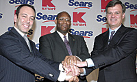 Kmart chairman Edward Lampert (left) and CEO Aylwin Lewis with Alan Lacy, current chairman and CEO of Sears, announce the merger of the companies.