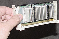 You can remove the carrier, CPU, and heat sink all at once, as shown here; or leave the plastic carrier in place, and remove just the CPU and heat-sink assembly.