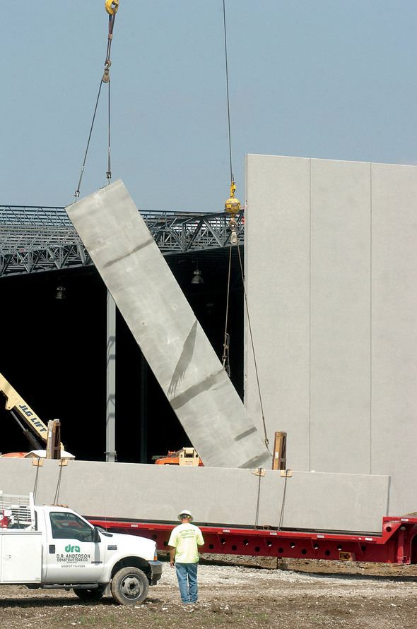 A crane lifts a section of the building's wall.