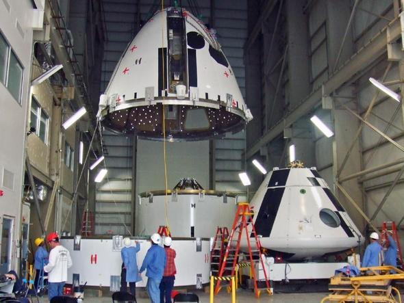 The four major structural components being positioned for assembly. At center, the boost skirt with the peak of the motor cage assembly visible above the gold rim. In the foreground, clockwise from top, is the forward fairing, crew module simulator, and coast skirt.