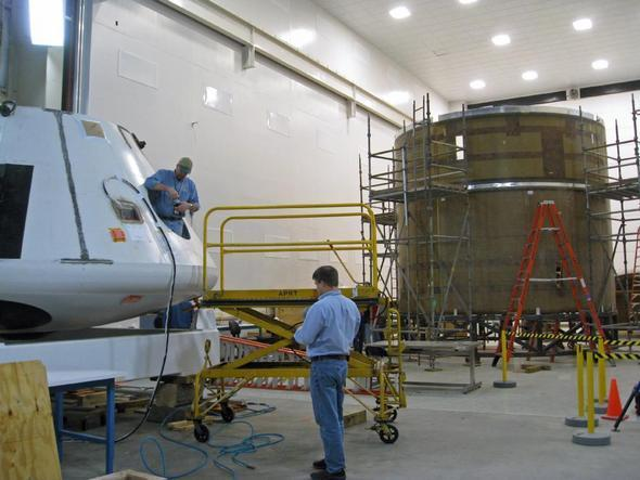 Workers attend to the crew module in the foreground while the lower sections of the test vehicle take shape in the background. The point of separation between the larger boost skirt and the coast skirt is the metallic strip visible just above the orange ladder.